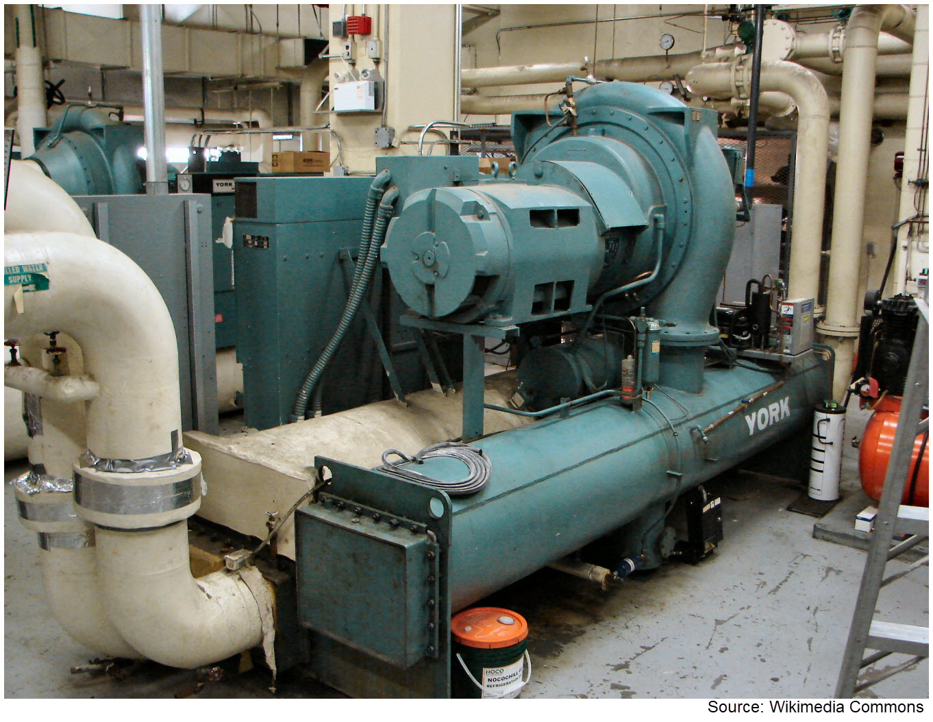 This is a picture of chiller equipment in a large utility room.